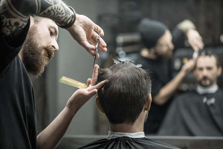unmatched: Unmatched barber with a big beard is cutting the hair ends of his client in the black cutting hair cape in the barbershop. Customer has hairgrips on the head. The both blurry reflected in the mirror. Stock Photo