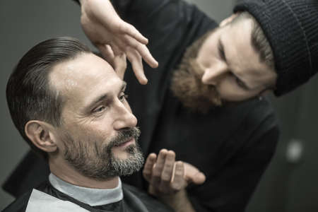 Joyful man with a beard in the barbershop. Bearded barber in a black T-shirt and a cap applies a shaving gel on clients skin. Closeup. Horizontal. Stock Photo