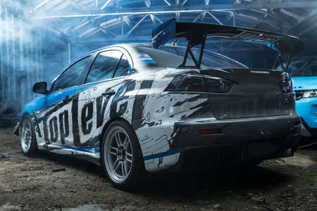 sportcar: Kiev, Ukraine - 14 May 2014: Mitsubishi Lancer Evolution X tuning sport-car. It colored in blue, black, whites colors with patterns and prints. Editorial photo. Shoot from the back.