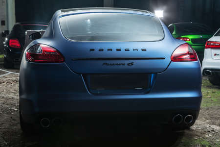 sportcar: Kiev, Ukraine - 14 May 2014: Porsche Panamera 4S tuning sport-car. It colored in blue matte color. Editorial photo. Shoot from the back. Editorial