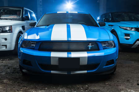sportcar: Kiev, Ukraine - 14 May 2014: Ford Mustang tuning sport-car. It colored in blue color with white stripes. Editorial photo. Editorial