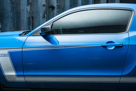 sportcar: Kiev, Ukraine - 14 May 2014: Ford Mustang tuning sport-car. It colored in blue color with white stripes. Editorial photo. Shoot from the side. Closeup.