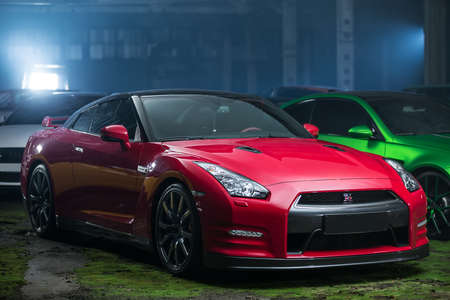 sportcar: Kiev, Ukraine - 14 May 2014: Nissan GT-R tuning sport-car on the background of other autos. It colored in red and black colors. Editorial photo.