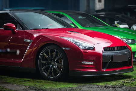 sportcar: Kiev, Ukraine - 14 May 2014: Nissan GT-R tuning sport-car. It colored in red and black colors. Editorial photo. Shoot from the side.