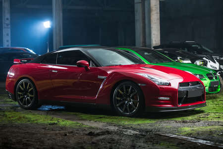 sportcar: Kiev, Ukraine - 14 May 2014: Nissan GT-R tuning sport-car on the background of other autos. It colored in red and black colors. Editorial photo. Shoot from the side.