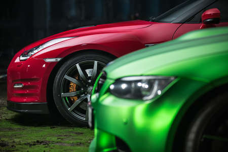 Kiev, Ukraine - 14 May 2014: Nissan GT-R tuning sport-car behind the green auto. It colored in red and black colors. Editorial photo. Closeup side view.