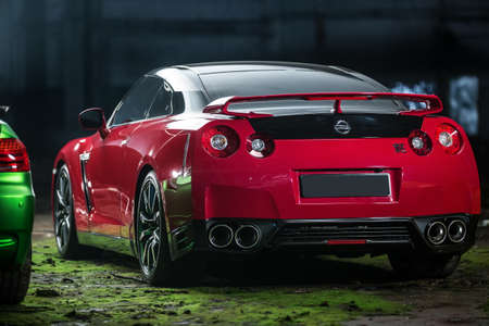 sportcar: Kiev, Ukraine - 14 May 2014: Nissan GT-R tuning sport-car. It colored in red and black colors. Editorial photo. Shoot from the back.