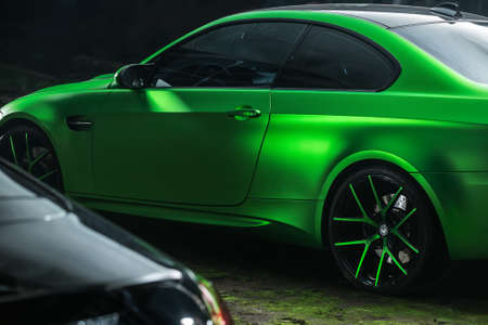 sportcar: Kiev, Ukraine - 14 May 2014: BMW M3 Coupe tuning sport-car. It colored in acid green color. Editorial photo. Shoot from the side.