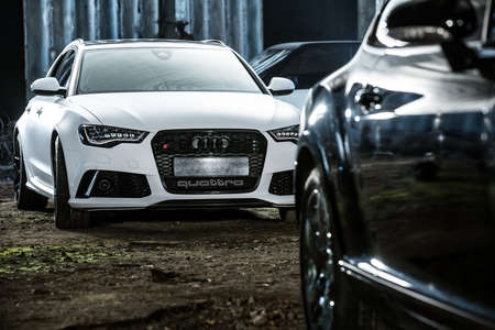 sportcar: Kiev, Ukraine - 14 May 2014: Audi RS6 tuning sport-car. It surrounded by other autos. Audi colored in white color. Editorial photo. Editorial