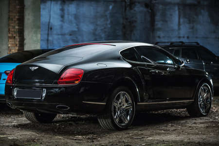 gt: Kiev, Ukraine - 14 May 2014: Bentley Continental GT Coupe tuning sport-car. It colored in black color. Editorial photo. Shoot from the back.