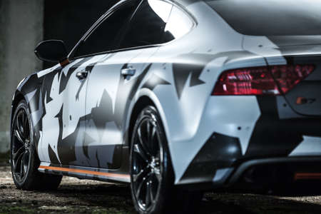 sportcar: Kiev, Ukraine - 14 May 2014: Audi S7 tuning sport-car. It colored in white, black, gray colors with patterns and orange stripes. Editorial photo. Closeup back side view.