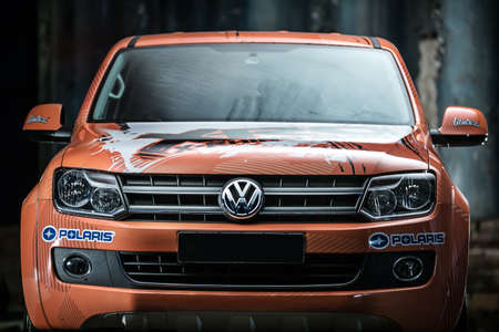 sportcar: Kiev, Ukraine - 14 May 2014: Volkswagen Amarok tuning sport-car. It colored in orange color with white and black prints. Editorial photo.  Closeup front view.