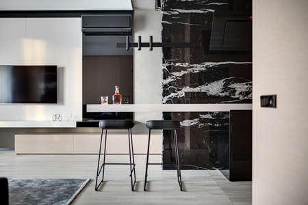 바닥에 마루가있는 현대 홀. 부엌 후드, 병 및 유리가 달린 탁상용 의자, 의자, 목재 로커, TV, 벽난로, 조절기 및 장식이있는 검은 색 대리석 벽이 있습 스톡 콘텐츠