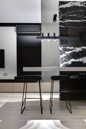Black marble wall with white patterns with a light tabletop and two black stools under it. There are glowing lamps, white wall with a TV, decorations, black fireplace with conditioner, wooden lockers. Zdjęcie Seryjne - 66954250