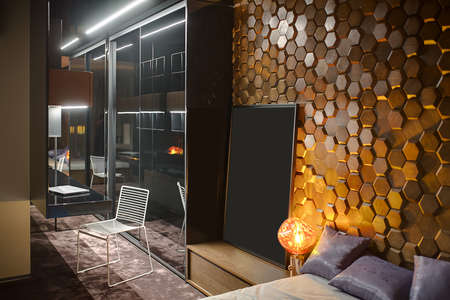 specular: Modern bedroom with a carpet on the floor and a wooden wall textured with hexagons. There is a specular wardrobe, a white chair, wooden lockers and shelves, a bed with pillows, glowing lamps.