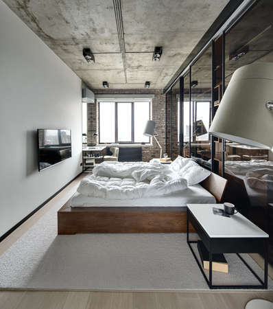 Bedroom in a loft style with brick wall and concrete ceiling. There is a TV, bed with pillows, lamps with lampshades, wardrobe with glass sliding doors, tables, armchair, carpet on the floor. 스톡 콘텐츠