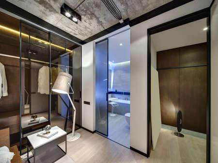 白い壁とコンクリート天井にロフト スタイルのインテリア。白熱ランプ、ガラス引き戸ワードローブ、テーブル、本、時計、トイレと廊下への扉が