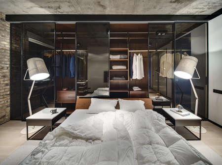 Loft style interior with brick wall and concrete ceiling. There is a bed with white pillows and blankets, glowing lamps, wardrobe with glass sliding doors, tables, parquet and a carpet on the floor. Stock fotó