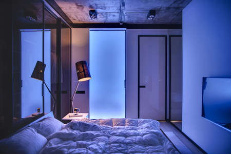 seeps: Low light bedroom in a loft style with light walls and concrete ceiling. There is a bed with pillows and blankets, table with book and clock, glowing lamp, TV. Light seeps through frosted glass door.