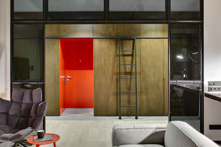 partitions: Luminous hall in a loft style with a red entrance door, wooden wardrobes and lockers, ladder with wheels, armchair, table with book and cup, sofa, glass partitions. Parquet and tiles are on the floor. Stock Photo