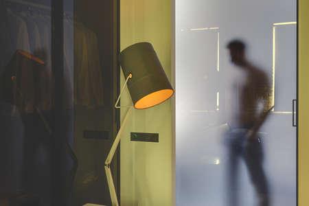 La silhouette de l'homme qui se cache derrière la porte vitreuse dépoli à l'intérieur moderne rougeoyant avec des murs jaunes. En face de la porte, il y a une lampe lumineuse avec un abat-jour orange et une cloison en verre.