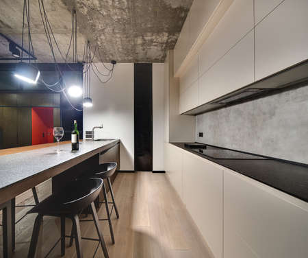 kitchen island: Kitchen zone in a loft style with a parquet on the floor. There is a kitchen island with sink and faucet, bottle and glass, black chairs, light lockers, dark tabletop with a stove, glowing lamps.