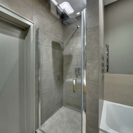 cabine de douche: Contemporary bathroom with long tiles on the walls and floor. There is a shower cabin with a glass door, white bath, door, chrome towel holder, glowing lamps. Vertical.