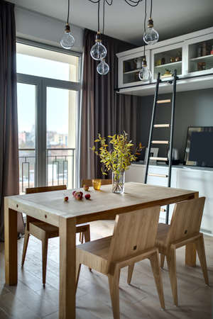 Wooden table with branches in the vase, apples, glass and  four chairs in the modern kitchen. There is white lockers and shelves with accessories, dark ladder, hanging lamps, glass door with a window. Zdjęcie Seryjne - 68507781