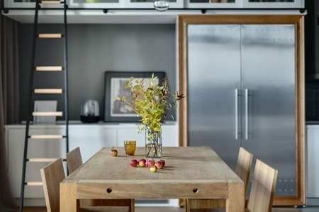 fridge lamp: Light wooden table with branches in the vase, apples, glass and  four chairs in the modern kitchen. There is white lockers, dark ladder, lamp, trendy big fridge with two doors. Wide aperture photo. Stock Photo