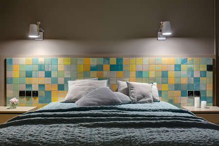 coverlet: Wide bed with many pillows and a coverlet on the background of the colorful tiles with black switches and power sockets. There are wooden nightstands with flower and candles, glowing white lamps.