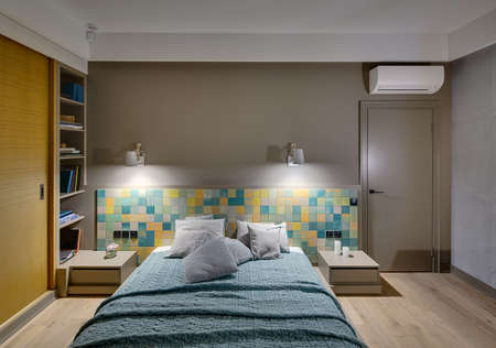 coverlet: Bedroom in a modern style with a large bed with many pillows and a coverlet on the colorful tiles background. There are two wooden nightstands, glowing lamps, shelves with books, wooden wardrobe.
