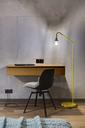 Wooden rack with a laptop and a black chair with a gray pillow on the background of the gray tiled wall. Next to the rack there is a glowing trendy yellow lamp. Black power sockets are on the wall. Zdjęcie Seryjne