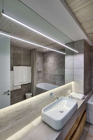 Contemporary bathroom with textured tiles and a wooden ceiling. There is a white sink on the rack, faucet, wooden lockers, mirror, towel, bath, door, wooden panel over the sink, glowing lamps, bucket. Stock Photo