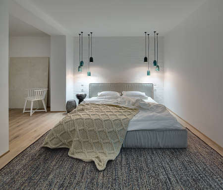 Bedroom in a modern style with white walls and a parquet with a carpet on the floor. There is a bed with a white pillows and blanket and brown plaid, nightstand with book and lampshade, lamps, chair.