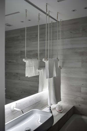 Cool bathroom in a modern style with light wooden walls and a white ceiling. There is a sink with faucet, big mirror, stylish white towel holders, white dispenser and glass vase with ear sticks.