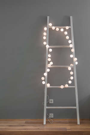 White ladder with glowing sphere lamps in a form of the garland on the gray wall background. There is a parquet on the floor and power sockets on the wall. Closeup. Vertical. Zdjęcie Seryjne - 68508291