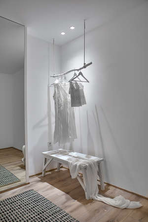 Room in a modern style with white walls and a parquet with a carpet on the floor. There is a white wooden hanger with hanging clothes, wooden bench with a shawl, mirror, glowing lamps. Vertical. Standard-Bild