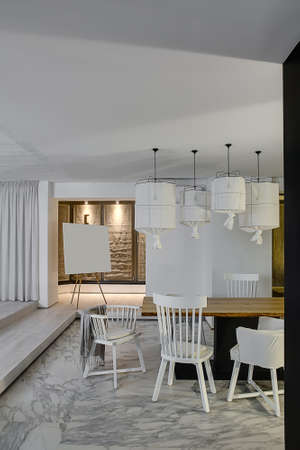 Room in a modern style with white walls and a parquet with gray tiles with patterns on the floor. There is a wooden table with white chairs, hanging lamps with white lampshades, curtain, easel.
