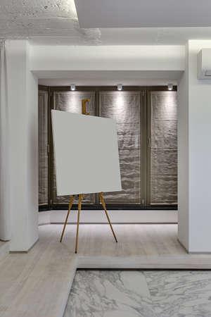 #68508297   Zimmer In Einem Modernen Stil Mit Weißen Wänden, Parkett Und  Hellen Fliesen Mit Mustern Auf Dem Boden. Auf Der Hölzernen Staffelei Steht  Eine ...