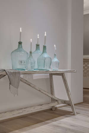 Glowing candles in the stylish bottles on the wooden table on the white wall background. There is a shawl near them. Behind the bottles there are power sockets on the wall. Closeup. Vertical. Standard-Bild