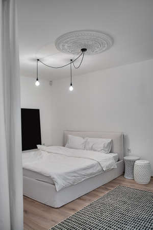 nightstands: Bedroom in a modern style with white walls and a parquet with a carpet on the floor. There is a bed with white pillows and a blanket, design nightstands, hanging glowing lamps, white bass-relief.