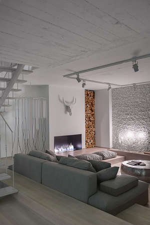 Hall in a modern style with white walls. There is a gray sofa with pillows, burning fireplace and candlesticks, pouf, decorative buffalo skull, white stair, walls decorated with firewood and pebbles.