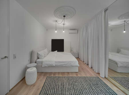 nightstands: Modern bedroom with white walls and a parquet with a carpet on the floor. There is a bed with white pillows and blanket, design nightstands, hanging glowing lamps, white bass-relief, mirror, curtains. Stock Photo