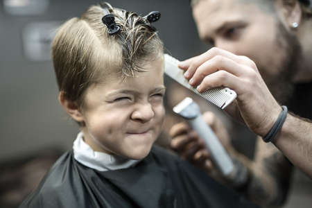 Small kid in barbershop Фото со стока