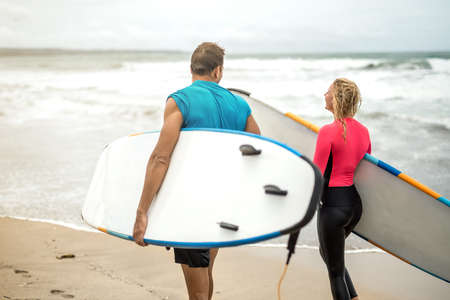 board shorts: Couple of surfers on oceans shore