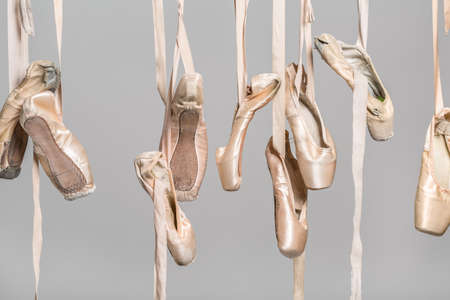 Several hanging beige ballet shoes on the gray background in the studio. Closeup. Horizontal. Stock Photo