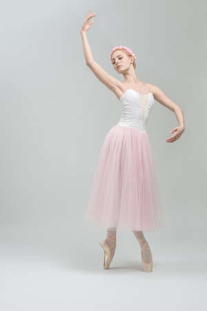 pointes: Young ballerina stands on pointes on the gray background in the studio. She wears a dance wear with white top and a rose skirt and has a wreath on her head. Her right hand is in the air. Vertical. Stock Photo