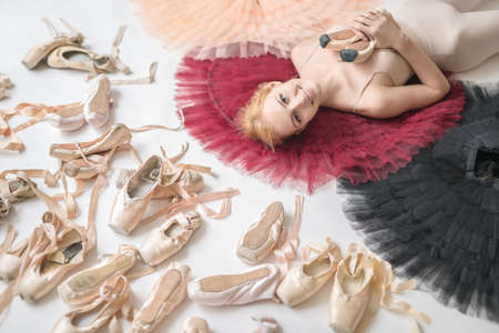 slippers: Smiling ballerina lies on the colorful tutus on the white floor
