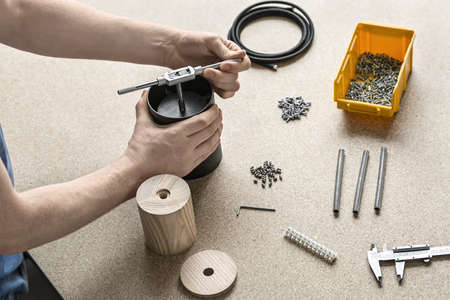 Man with tattoo is using a t-wrench on a black metal cylinder on the light table. On the table there are wooden billets, cable, plastic box with screws, tools, caliper, bushings, connector. Closeup.