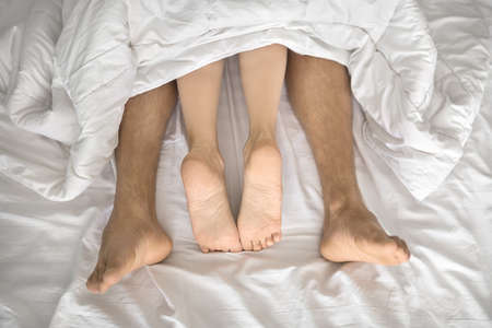 Twosome under the white blanket on the bed. Their barefoot legs are sticking out the blanket. Indoors. Closeup. Horizontal. Stock Photo